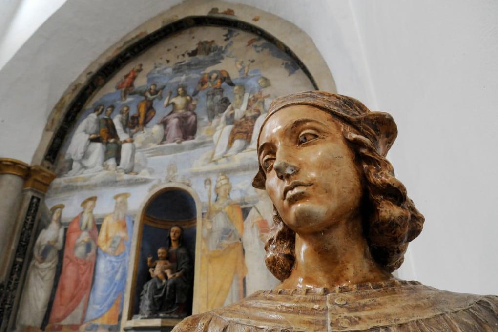 Il busto di Raffaello e, sullo sfondo, un suo affresco presso la Cappella San Severo a Perugia.
