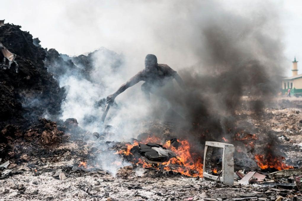 Un normale giorno di lavoro ad Agbogbloshie: i fumi tossici scoperchiano i fili metallici dei rifiuti elettronici.