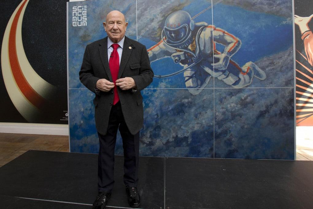Alexei Leonov, il primo uomo a trovarsi fuori da una navicella spaziale, il 18 marzo 1965, davanti al poster che celebra l'impresa, al Museo delle Scienze di Londra.