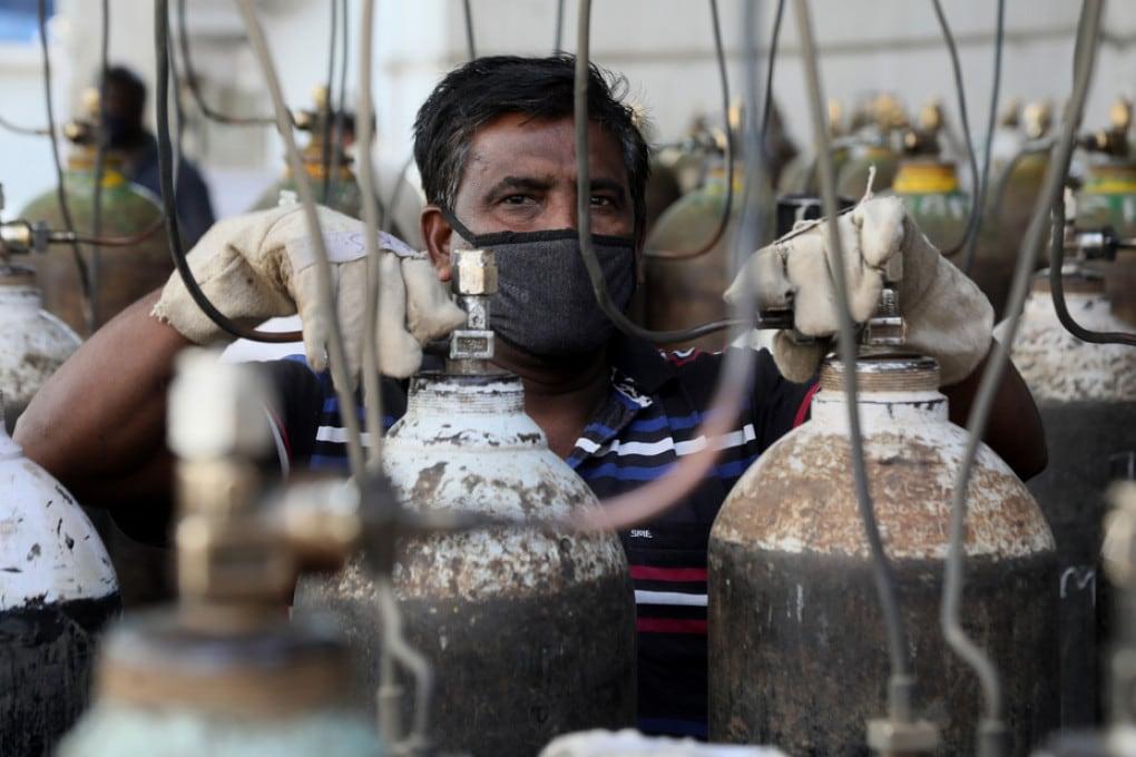 Un lavoratore ricarica le bombole di ossigeno per i pazienti malati di covid in India.