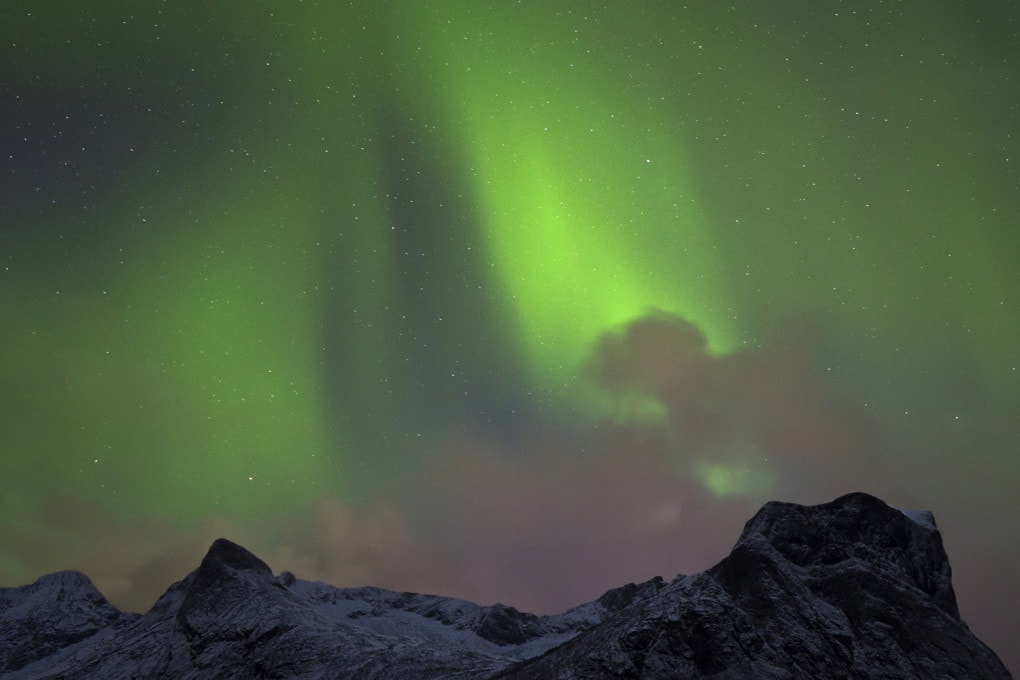 Un'aurora boreale fotografata da un lettore di Focus il 19 ottobre 2019 dall'isola di Senja, in Norvegia. Una esposizione di 20 secondi ha aiutato a schiarire la neve sulle montagne grazie a una Luna appena sorta e bassa nel cielo abbastanza nuvoloso.