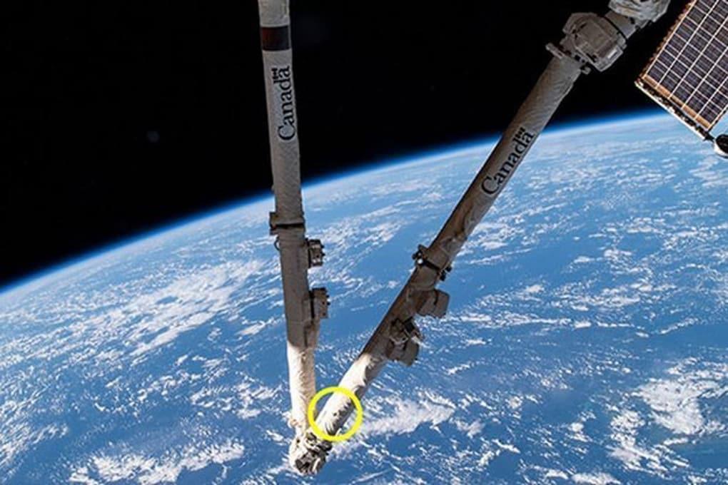 Il braccio robotizzato della Stazione spaziale, il Canadarm2: nel cerchio giallo il foro provocato da un frammento di spazzatura spaziale.