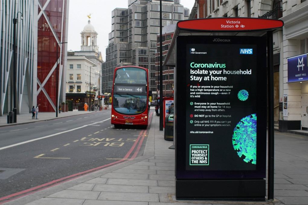 Una fermata dell'autobus di Londra, con un pannello a messaggio variabile che ricorda le misure da adottare per contenere la pandemia.