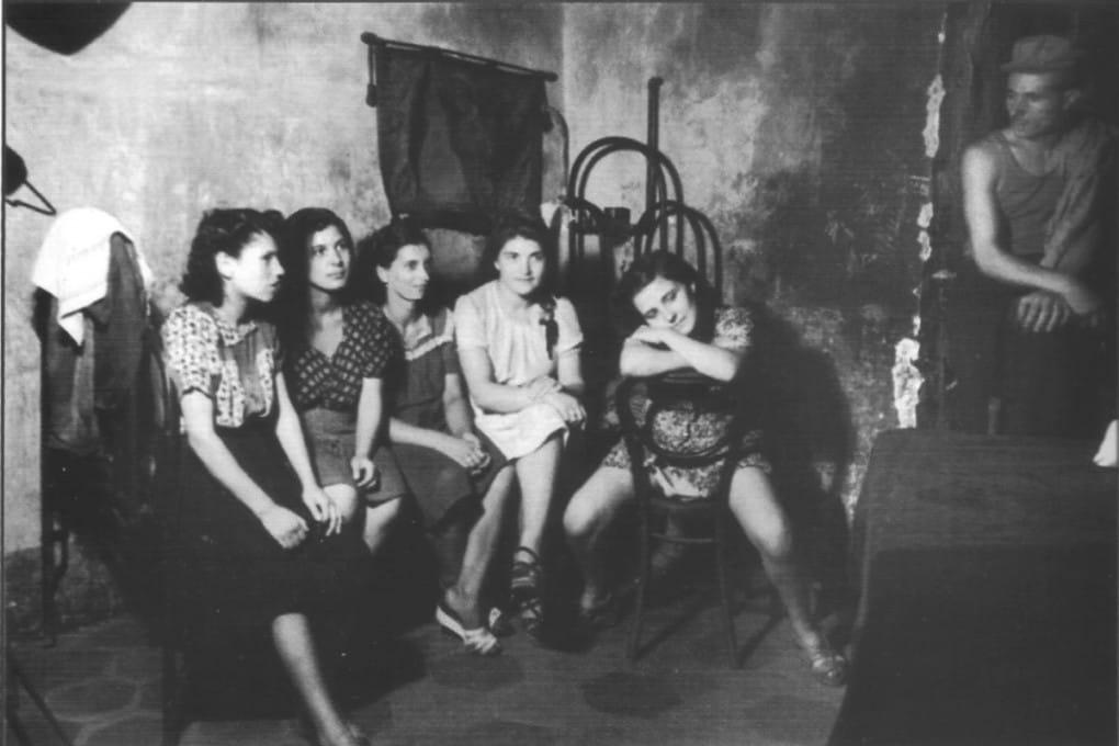 Interno di una casa di tolleranza a Napoli nel 1945. Il 29 gennaio 1958 venne approvata alla Camera la legge, presentata da Lina Merlin, che stabiliva la chiusura delle case di tolleranza in Italia. La legge entrò in vigore a marzo e impose che alla mezzanotte del 20 settembre 1958 venissero chiuse oltre 560 case di tolleranza distribuite su tutto il territorio nazionale.