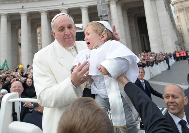 Il mini Papa e gli altri bambini (disperati) in braccio ai potenti