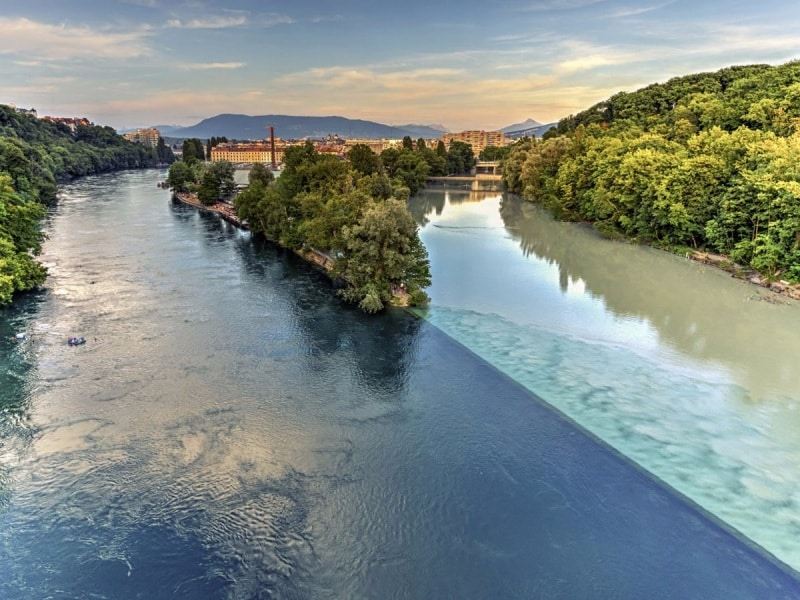 in-geneva-travelers-can-witness-the-majestic-sight-of-two-rivers-colliding-with-one-another-the-rhone-river-starts-in-lake-lehman-while-the-arve-river-is-fed-by-glaciers-in-the-chamonix-valley-when-the-two-bl