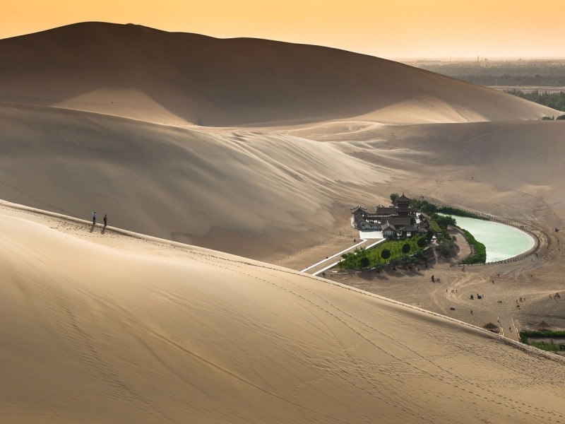 the-crescent-lake-or-yueyaquan-in-chinese-is-a-fresh-water-spring-in-the-shape-of-a-half-moon-that-sits-in-the-gobi-desert-the-oasis-is-believed-to-have-existed-for-around-2000-years-though-it-has-seen-its-wa